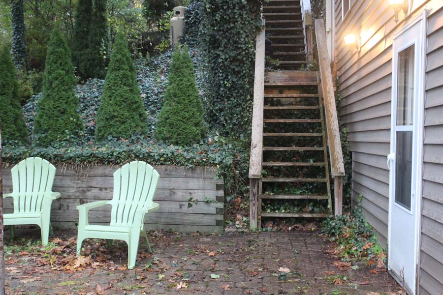 Stairs down to property with paver patio leading to green lawn area